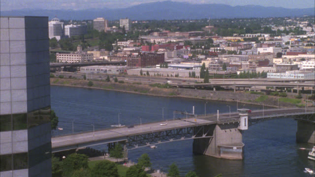 pan left to right of portland oregon skyline from behind glass window of high rise building. cars driving on highway next to willamette river in fg, hills and snow-capped mount hood mountain in bg. cities. cityscape. morrison bridge. hawthorne bridge. - portland oregon stock videos & royalty-free footage