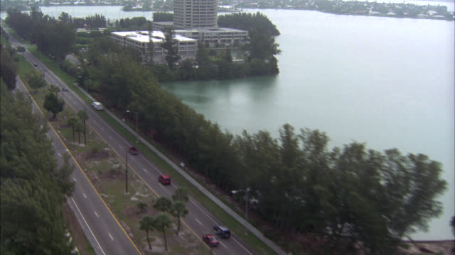aerial over downtown sarasota, florida. pov moves over ocean, beach, cars driving on city streets and buildings, houses. pass boats, sailboats on water and  docked in harbors or marinas. cities. - florida usa stock-videos und b-roll-filmmaterial