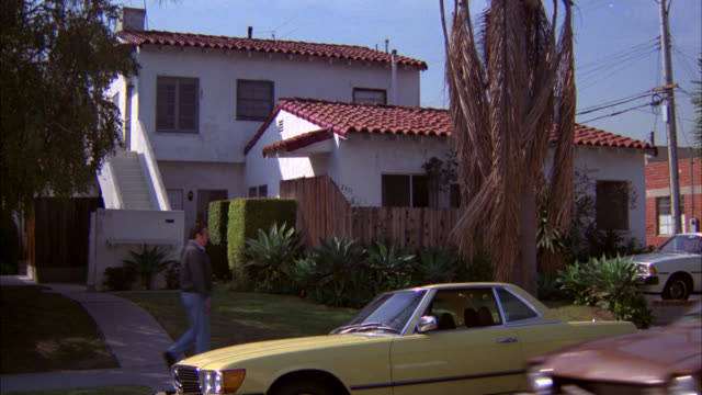 zoom in on two-story apartment building or house. spanish style roof. white stairs. middle class. palm tree and yellow mercedes coupe parked outside. - 1981年点の映像素材/bロール