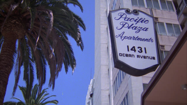 """up angle to tall apartment building with palm trees in front. sign reading """"pacific plaza apartments 1431 ocean avenue."""" - ocean avenue stock videos & royalty-free footage"""