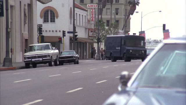 medium angle of city street as swat truck or van turns corner  with flashing lights and swerves to curb. christian science reading room and adult theater in bg. cars parked on curb. - 1975 stock videos and b-roll footage