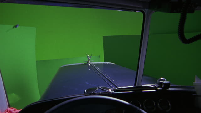 medium angle out the driver's side through the windshield of a vintage car, probably from the 1920s.  a pair of sunglasses on the dash.  green screen special effect. - special effect stock videos & royalty-free footage