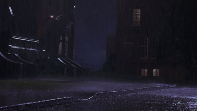 wide angle of a street corner, maybe part of a church or a university or college campus. rain pours from the sky onto the brick buildings.  raining, college campus. storms. actual location is bishop's university. - 公共の建物点の映像素材/bロール