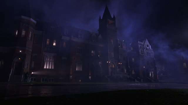 stockvideo's en b-roll-footage met wide angle of a large brick building at night in the rain.  could be a university or college campus. looks like a haunted house or mansion in a storm. a large tower can be seen in the middle of the building.  could be a private school.  fog moves through - landhuis