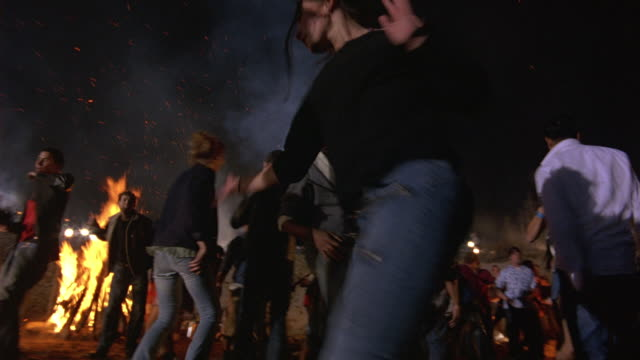 hand held pan through of teenagers or young adults dancing in the sand around bonfires. couples dance really close together. could be used for high school, college, fraternity, or sorority party. men. women. - organised group stock videos & royalty-free footage