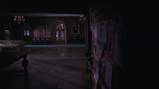 WIDE ANGLE OF MEETING HALL IN MANSION, MANOR, UNIVERSITY OR ACADEMY BUILDING. UPPER CLASS. COULD BE PRIVATE SCHOOL. GOTHIC STYLE DOORWAYS, CANDLES, AND CHANDELIERS. PAINTINGS ON WALLS.