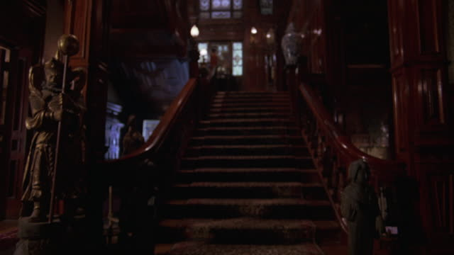 WIDE ANGLE OF STAIRCASE IN UPPER CLASS MANSION OR MANOR. RAILINGS AND LIGHTNING FLASHES IN BACKGROUND. EXOTIC-LOOKING STATUES NEXT TO BASE OF STAIRS.
