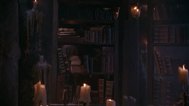 vidéos et rushes de medium angle of bookshelves covered with cobwebs and candles. could be haunted house, rustic mansion or manor. - fantasmagorie