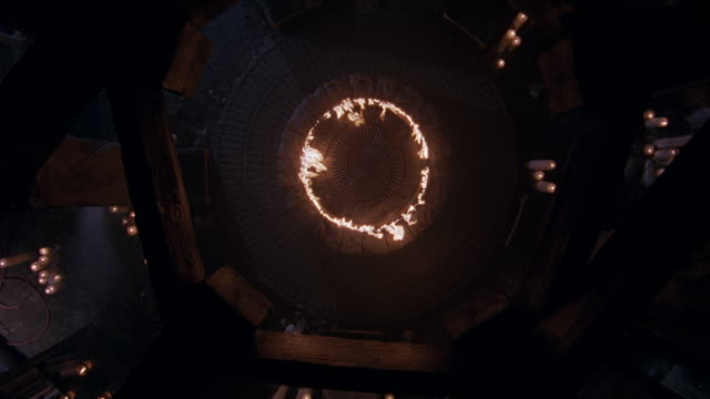 high angle down through ceiling rafters. birdseye pov. ring of fire in center of pentagon-shaped worship area. camera rotates 360-degrees and moves in on fire. candles, circular and spiral carvings surround fire. could be haunted house. fire stops at end - domestic room stock videos & royalty-free footage