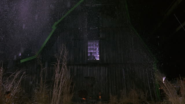 wide angle of barn or barnyard. wood panels, ladders, and tools. blue screen lining roof of barn. stunt man visible through glass window. runs forward and breaks through glass, falls to ground directly in front of camera. - 干し草点の映像素材/bロール