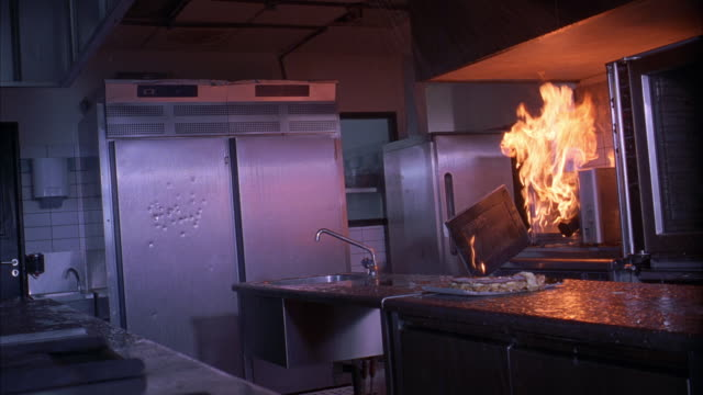 medium angle of industrial kitchen in restaurant or hotel. bullet marks and holes on refrigerator. flames of fire billow out of microwave.  water leaks from ceiling. sinks, pots, pans, stovetops visible. - microwave stock videos & royalty-free footage