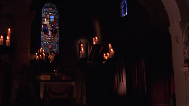wide angle of church or chapel. altars surrounded by candles and religious statues. stained glass windows visible. - 礼拝堂点の映像素材/bロール