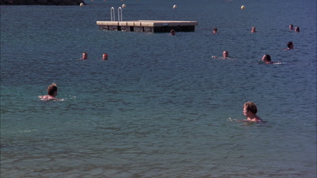 wide angle of swimmers and people swimming in ocean near bay or harbor. diving platform. ocean. - diving platform stock videos & royalty-free footage