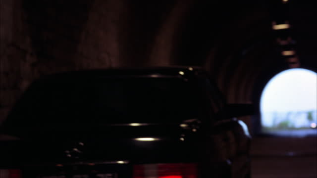 tracking shot following a mercedes-benz car as it drives through a tunnel.  the sedan has a near miss with another car in the tunnel.  almost a car accident. near collision. - near miss stock videos and b-roll footage