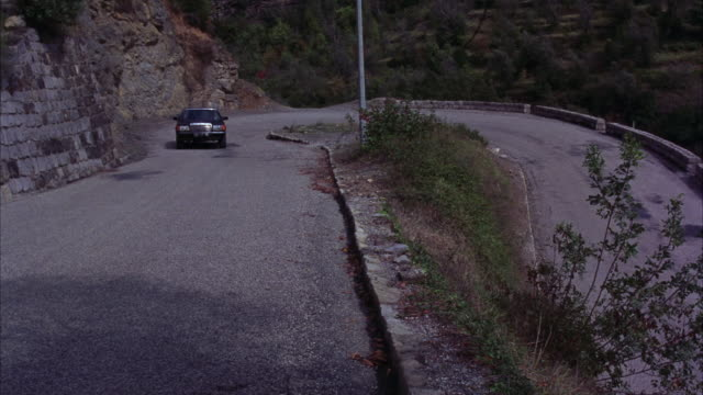 high angle down on a road in a rural area as a mercedes sedan car drives around a hairpin turn, followed by a yellow motorcycle. could be a car chase. - mercedes benz stock videos and b-roll footage