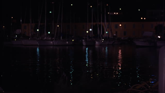 medium angle of a man jumping into the water at a dock or dock.  boats, mostly sailboats, in the background. - small boat stock videos & royalty-free footage