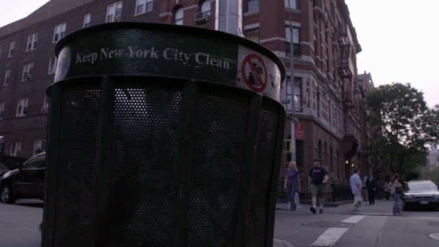 "PAN UP FROM TRASH OR GARBAGE CAN ON STREET CORNER TO MIDDLE CLASS MULTI-STORY BRICK APARTMENT BUILDING. PEDESTRIANS, PEOPLE WALKING ON SIDEWALK. MANHATTAN.<P><A HREF=""HTTPS://WWW.SONYPICTURESSTOCKFOOTAGE.COM/FOOTAGE?KID=4370"">FOR DAY-NIGHT MATCHING SHOTS,"