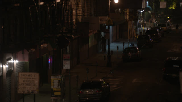 high angle down of orchard st. people, pedestrians walking on sidewalks. cars parked. multi-story apartment buildings. urban area. city streets. lower east side. parking meters. fire escapes. - 非常階段点の映像素材/bロール