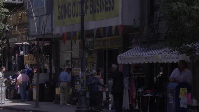 """zoom in on store with """"going out of business"""" sign. cars and taxi cabs on city street. people walking, pedestrians on sidewalk. storefronts and shops on first floors of multi-story brick apartment buildings. - 2008 stock videos & royalty-free footage"""