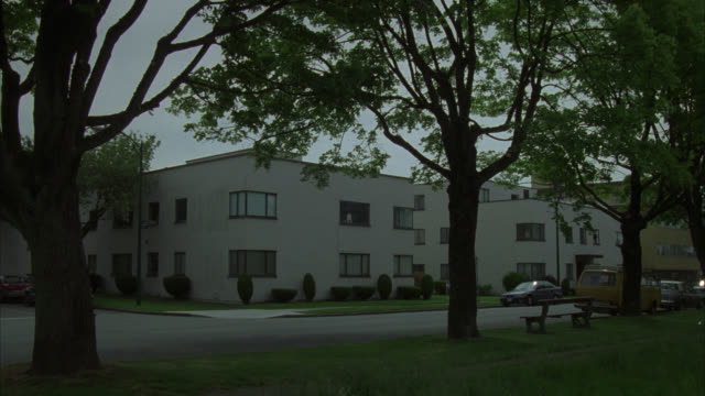 wide angle of two-story apartment building or townhouse across street from park. cars parked on curb. trees line street. park bench. could be lower-middle class residential area. - anno 1994 video stock e b–roll