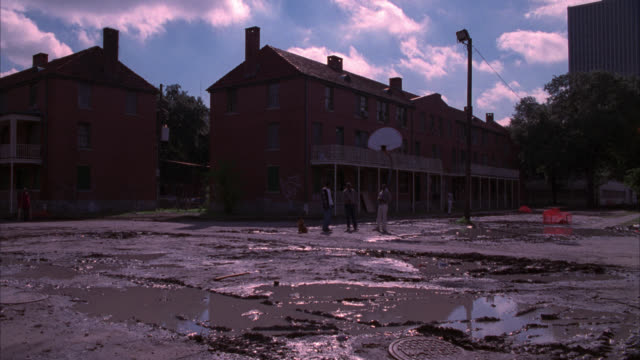 wide angle of lower class housing projects. three-story brick buildings. children play and talk in muddy lot in fg. could be school. basketball hoop or net. - new orleans stock videos & royalty-free footage