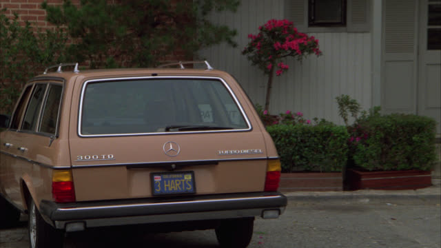 "PULL BACK FORM MERCEDES STATION WAGON CAR PARKED AT "" GROVE MEDICAL CLINIC ."" LICENSE PLATE READS ""3 HARTS."""
