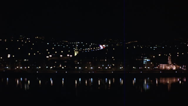 pan left to right across the danube river.  the buda castle and the chain bridge can be seen.  cars drive down a road or freeway - royal palace of buda stock videos & royalty-free footage