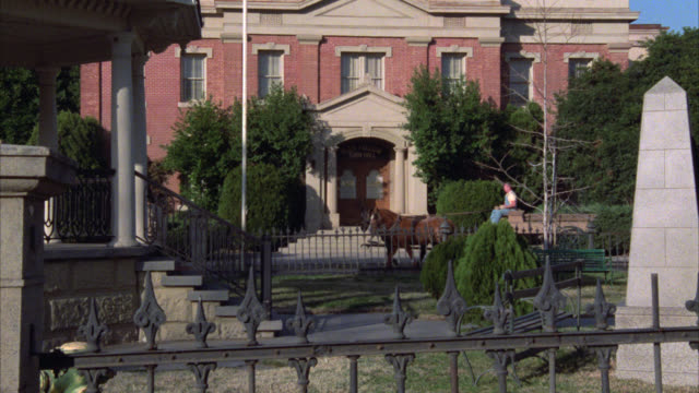 pan right to left from view of town hall over wrought iron fence to monument and gazebo in park. camera continues to pan to tudor style house. horse and wagon trots by. pedestrians walk through small town. town squares. - gazebo stock videos & royalty-free footage