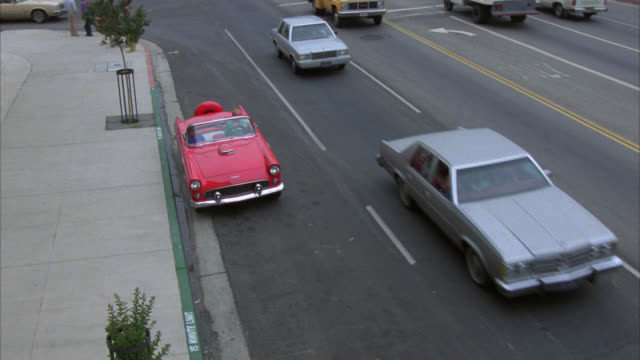 pan left to right as red aston martin convertible drives down street in studio city north of los angeles. cars drive down street. billboards in bg. stores, shops, and restaurants line street. - red convertible stock videos & royalty-free footage