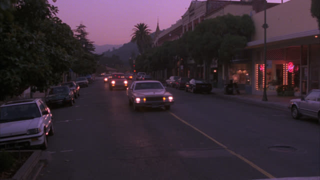wide angle of small town street as dusk. storefronts and shops line street. cars with headlights on drive down street; others parked at curb. trees and palm trees. note: matches: 1241-b for dx and 1241-c for nx - dusk stock videos & royalty-free footage