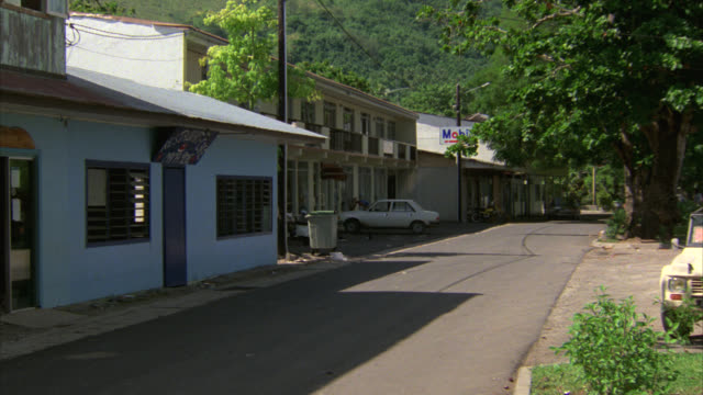 vidéos et rushes de medium angle of tropical town street. could be hawaii. mercedes drives down street. pedestrians walk on sidewalk. mountains and trees in bg. buildings. could be hotels, restaurants, or shops. - tahiti