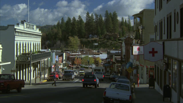 stockvideo's en b-roll-footage met wide angle of small town main street. could be colorado. trees or woods in bf. pine trees. hotel on left of frame. hospital or red cross on right of frame. cars drive on street. other cars parked on curb. could be mountain town. - straatnaambord