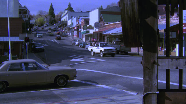vídeos y material grabado en eventos de stock de wide angle small town street. cars drive down street; others parked on curb. storefronts and shops. - california del norte