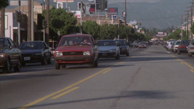vídeos y material grabado en eventos de stock de wide angle of city street with traffic. cars and truck drive down street. could be los angeles. mountain in bg. - 1980 1989