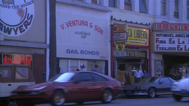 "wide angle "" v. ventura and sons bail bonds"" office, urban area. downtown. actual location is lankersham blvd. el portal movie theater on right with marquee advertising spanish language film. matches matching nx shot is 1345-c  dx is 1345-b. north hollywo - boulevard stock videos & royalty-free footage"