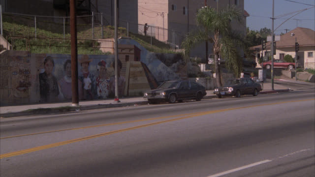 pan right to left as dodge ram truck turns onto street from residential area. could be small town. could be pasadena. wall with graffiti or art in bg. cars parked on curb. school bus drives by. - anno 1989 video stock e b–roll