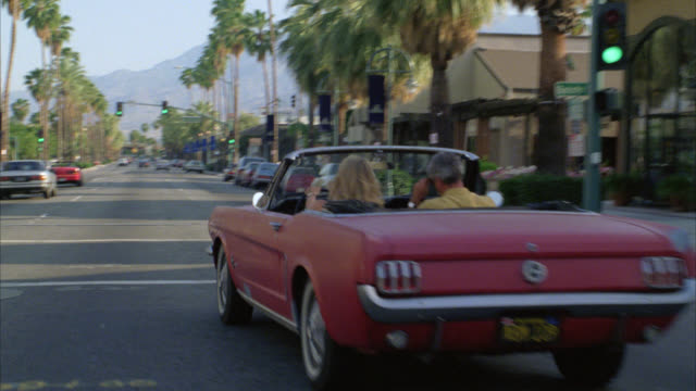 TRACKING SHOT OF CITY STREET IN PALM SPRINGS. COULD BE CITY OR TOWN.  PALM TREE LINED STREET. CAMERA FOLLOWS CONVERTIBLE PINK FORD MUSTANG. CARS PARKED ON CURB. BANNERS ON STREET LIGHTS.