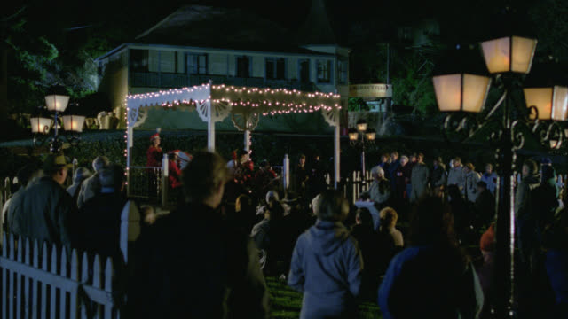 wide angle of outdoor concert gazebo in small town. local band or marching band in uniforms. people listen and mingle.  lamp posts in fg.  another angle is 1438-b - marching band stock videos & royalty-free footage
