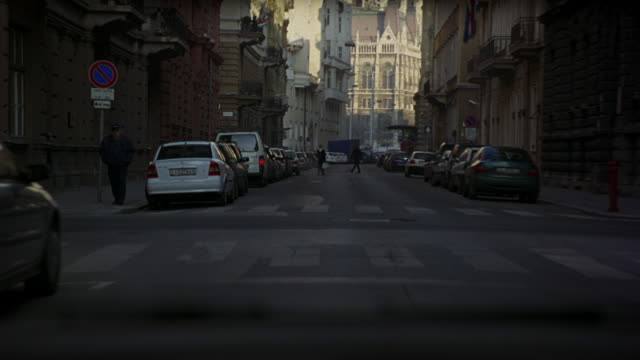 wide angle driving pov straight forward of city streets of budapest lined with parked cars. passes pedestrians and trolley or streetcar. stops at red stoplight or traffic signal behind vw volkswagen passat with hungary license plate. - volkswagen stock-videos und b-roll-filmmaterial