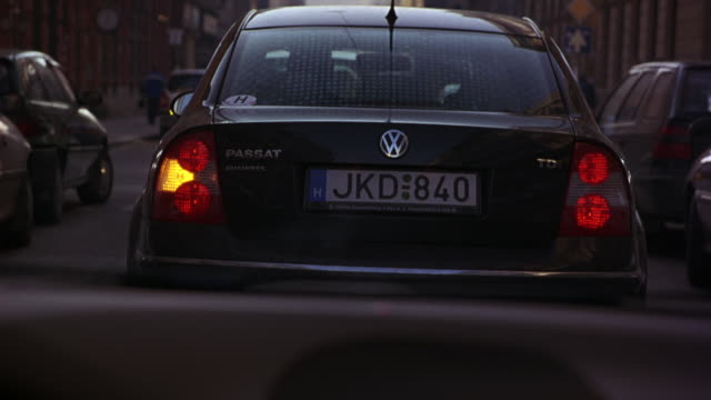 wide angle driving pov straight forward of city streets of budapest lined with parked cars. passes apartment buildings, street signs and pedestrians. follows volkswagen passat with hungary license plate. - volkswagen stock-videos und b-roll-filmmaterial
