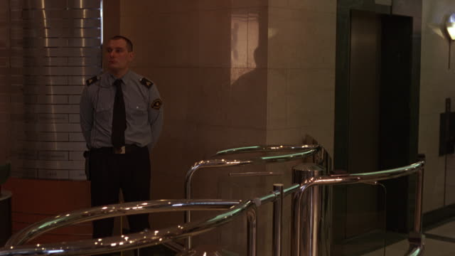 wide angle of lobby area. security guard stands between turnstile entrance and elevators. elevator door opens as business man swipes security id and enters. - guardia di sicurezza video stock e b–roll