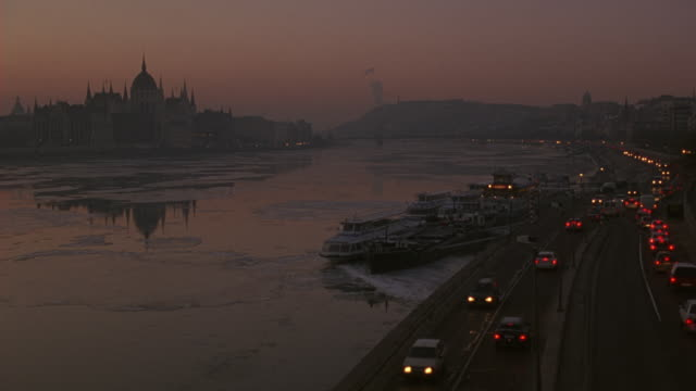 pan right to left from a highway or road to the danube river with the hungarian parliament building in the background.  could be dusk. an icy river filled with ice. - budapest video stock e b–roll