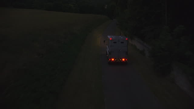 aerial tracking shot of mercedes-benz vario military personnel vehicle or truck driving on narrow road through french countryside. truck headlights are on. truck passes grassy field and disappears under canopy of trees. could be armored car chase. - mercedes benz stock videos and b-roll footage