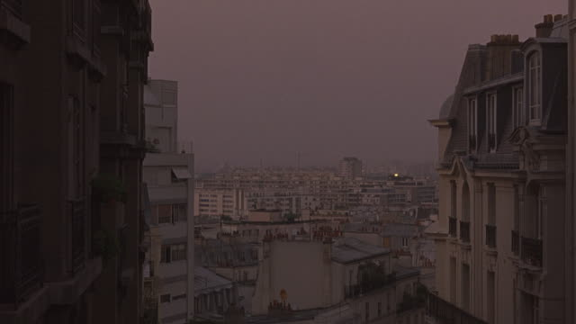 wide angle of paris skyline from upper floor of building. multi-story buildings, 19th century architecture, dormer windows. street lamp. cities. europe. could be hotels or apartments.  matching. - building storey stock videos and b-roll footage