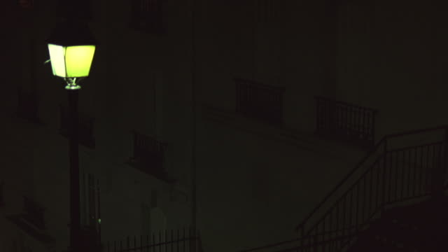 medium angle of street lamp next to multi-story brick building. stairway or staircase with metal railing in fg. building could be apartments or hotel. closed window have metal railings. - île de france stock-videos und b-roll-filmmaterial