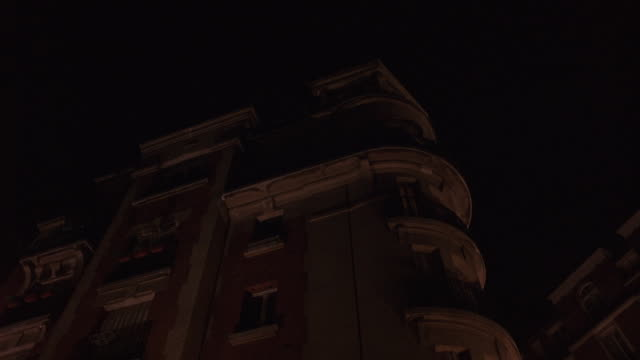 pan up of multi-story apartment building. camera rises past corner windows with iron railings on balconies. steps in background lead up hill towards large dome and tower of church. light can be seen on through closed shutters in top apartment. city street - stereotypically upper class stock videos & royalty-free footage