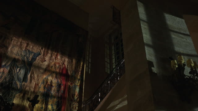 UP ANGLE OF LARGE TAPESTRY HANGING ON WALL IN DARK MANSION OR CASTLE. STAIRCASE AND RAILING ACROSS FROM THE TAPESTRY. CANDELABRA HANGS ON WALL. TAPESTRY APPEARS TO DEPICT SEVERAL PEOPLE STANDING BENEATH CRUCIFIX. RELIGIOUS THEMES. ART.