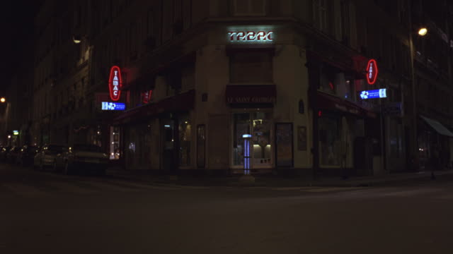 WIDE ANGLE OF PARISIAN STREET CORNER. NEON SIGNS LINE THE BUILDINGS AND CARS ARE PARKED ALONG SIDEWALK. THREE DUMP TRUCKS ENTER FROM LEFT TO RIGHT, STOP AND BLOCK STREET.