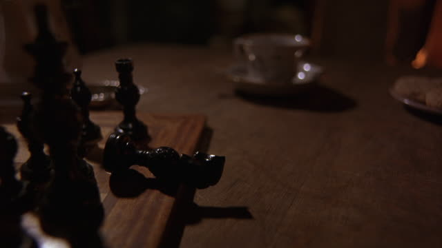 stockvideo's en b-roll-footage met close angle of chess board game. knight chess piece is sideways. teacup with saucer in background. - schaakstuk