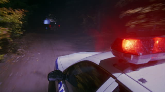 tracking shot of a police car chase.  the car races after a suv type car through a moonlit forest dirt road. - police car stock videos & royalty-free footage